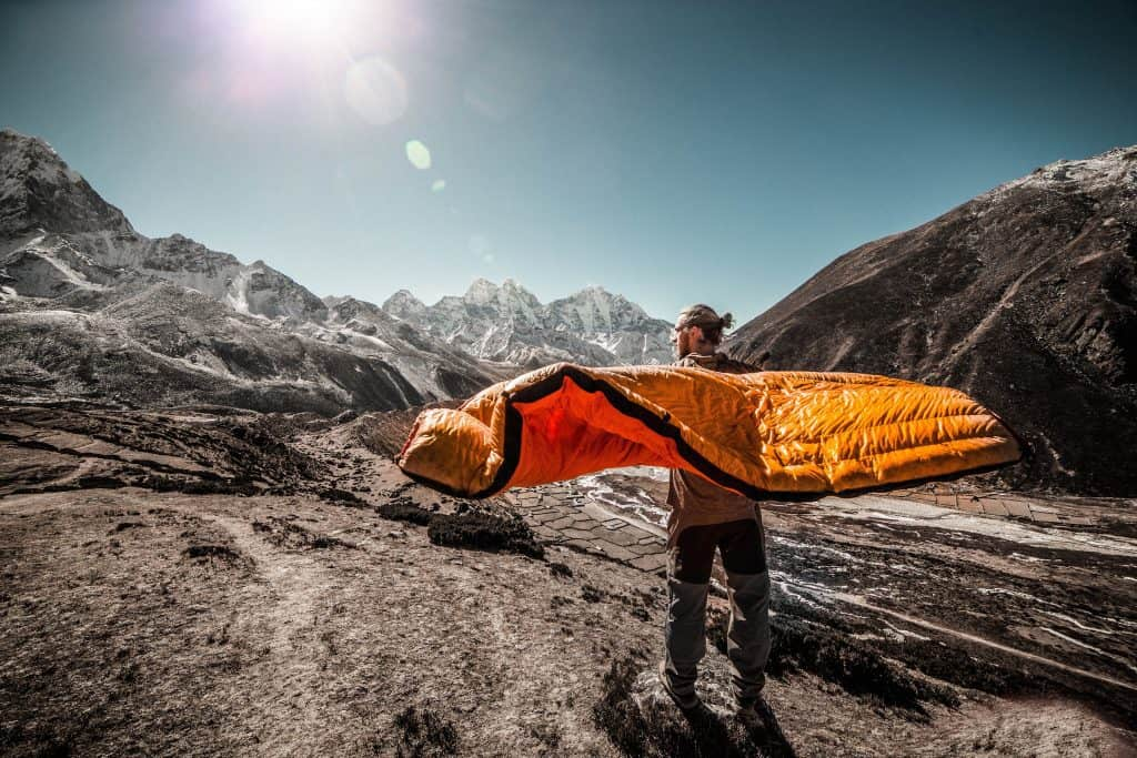 Man holding a bivy like a cape