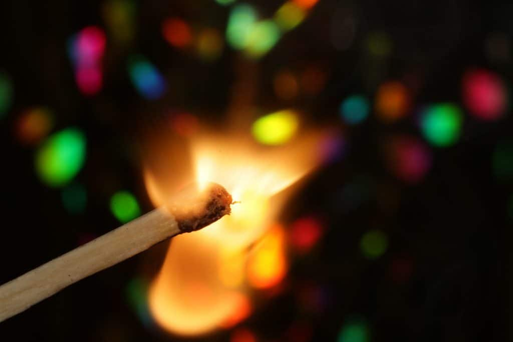 Photo of a match stick lighted up with different colors in the background