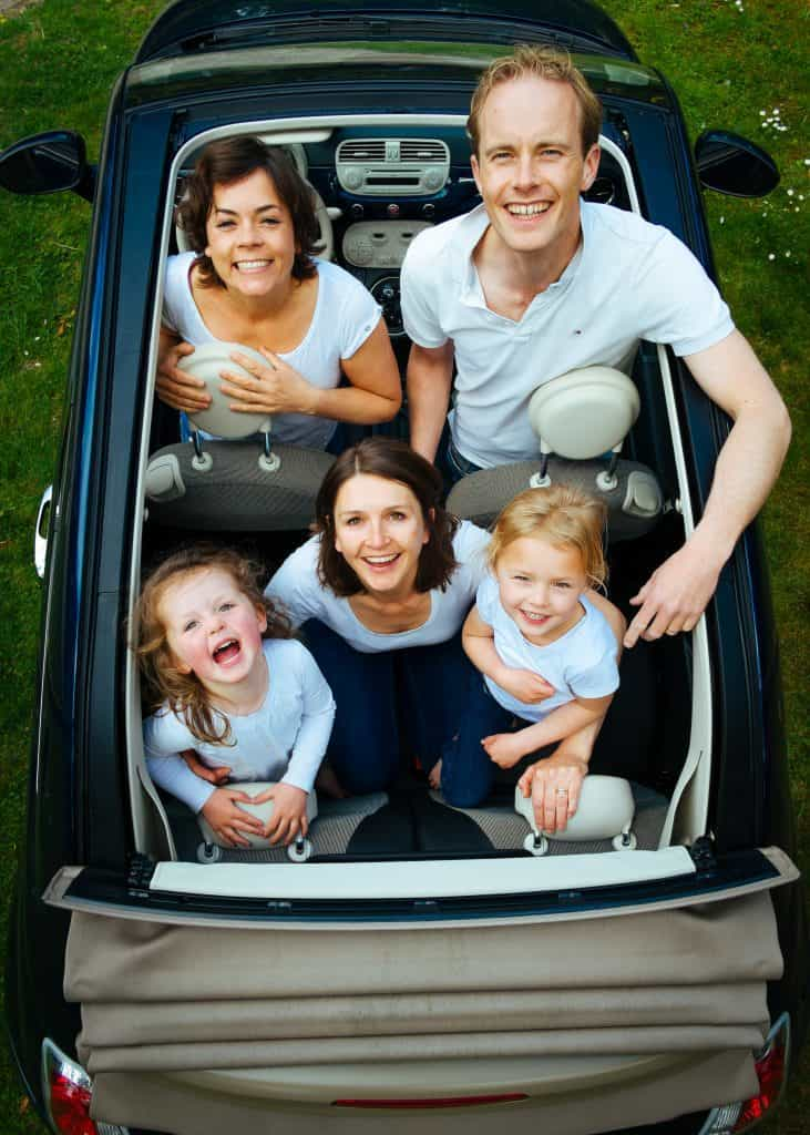 Photo of a family in a convertible car happy smiling