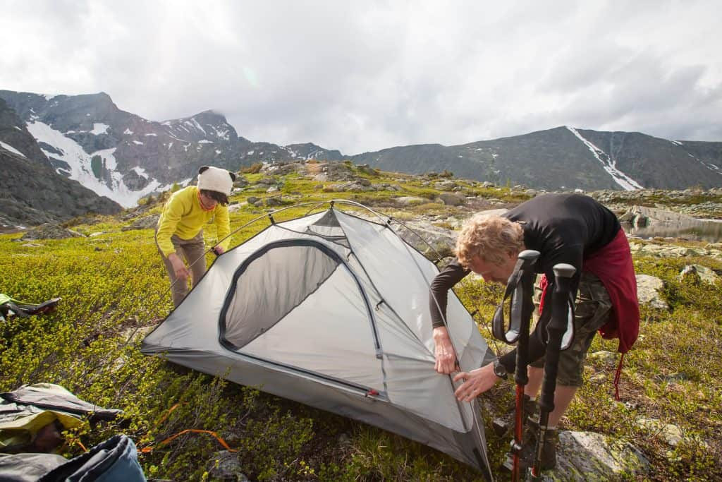 Backpackers are setting tent in mountains