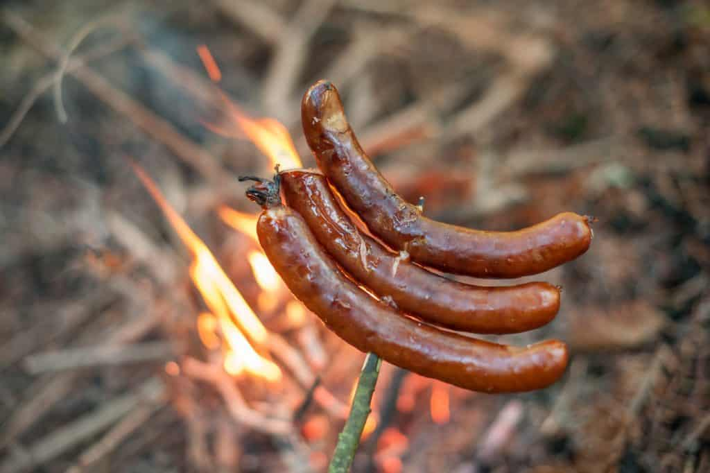 Photo of sausage roasted on camp fire