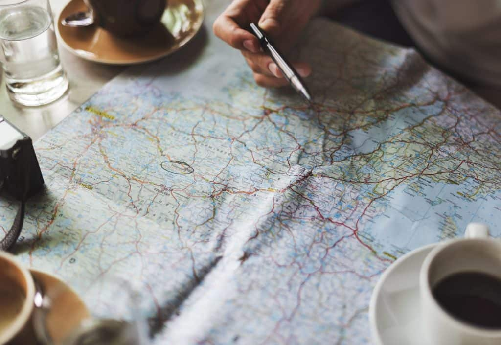 Photo of Map with beverages around it and a pen on a hand