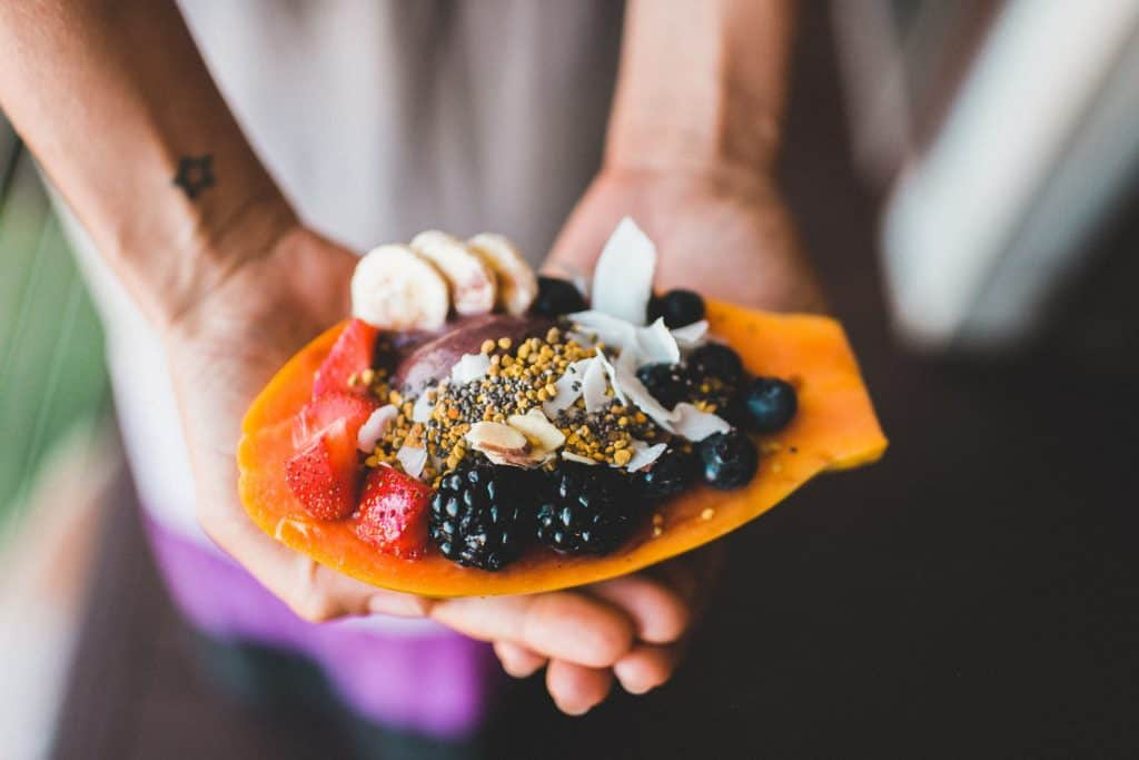 Photo of Delicious mixture of fruits dessert on someone's hand