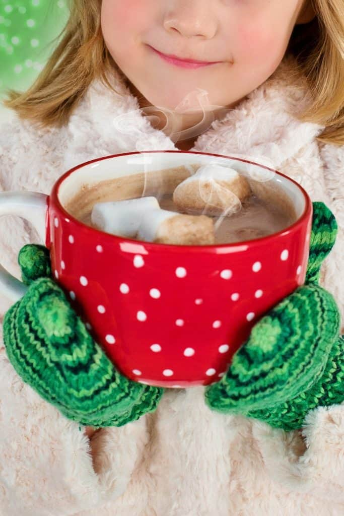 Girl wearing mittens holding a cup of hot chocolate