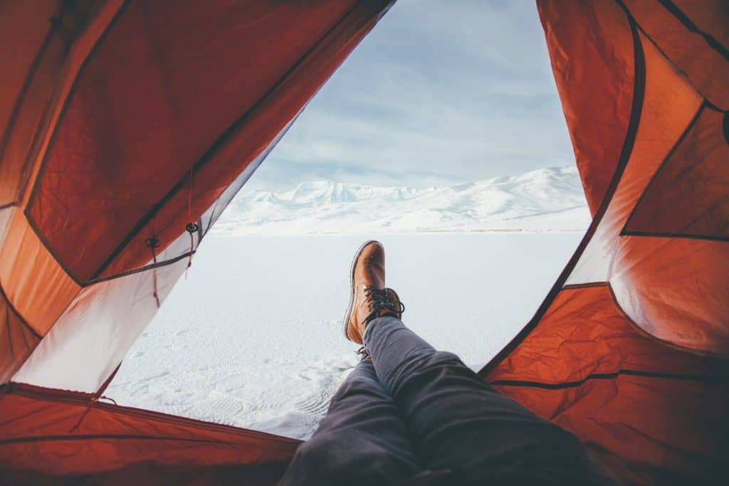 Camper enjoying his view outside tent of the snowy landscape