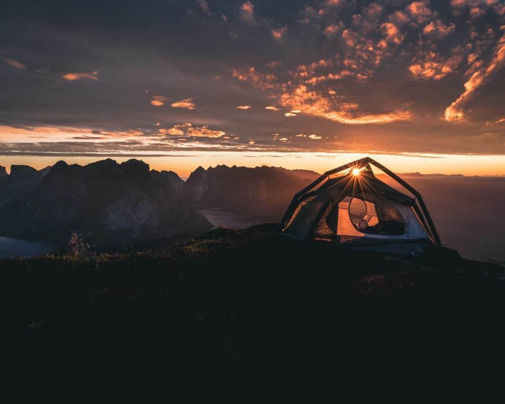 Tent overlooking a mountainous landscape during sunrise