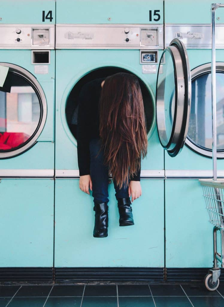 Comedic image of a woman stuck in a laundromat